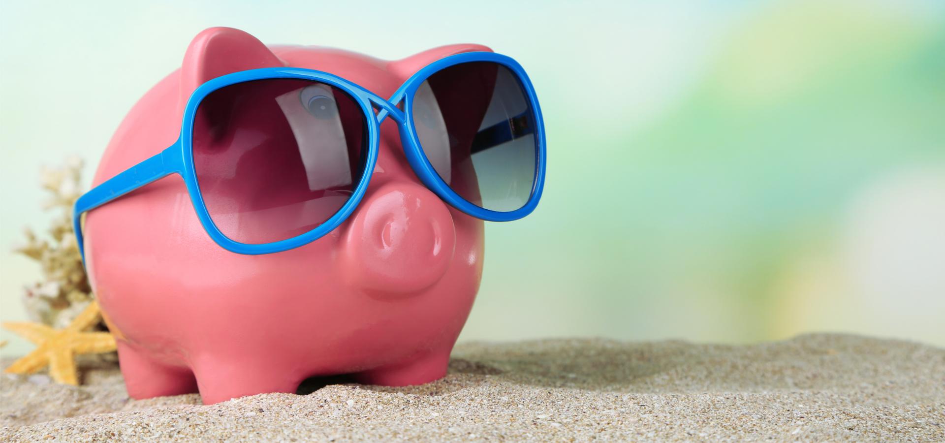 Piggy bank in sunglassess on beach